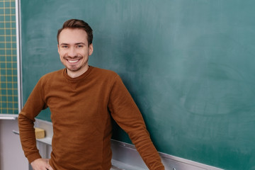 Young smiling man standing by blackboard