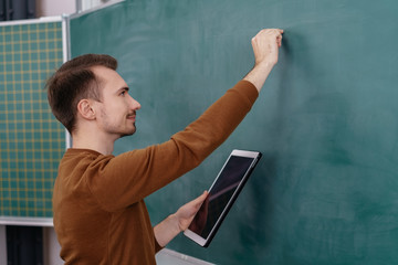 Male teacher or mature student writing on a board