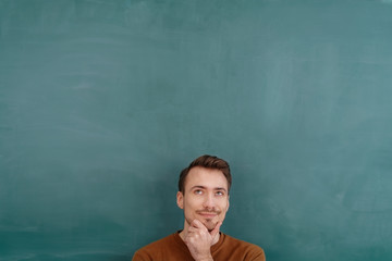Young thoughtful man standing against blackboard