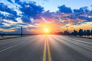 Empty asphalt road and city skyline at sunset
