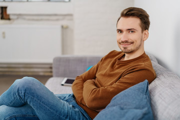 Young smiling man sitting on sofa at home