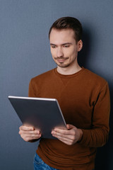 Man using digital tablet against dark wall