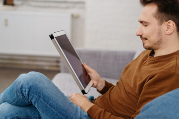 Young man using digital tablet at home