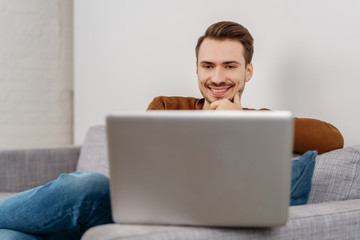 Young cheerful man sitting with laptop on sofa