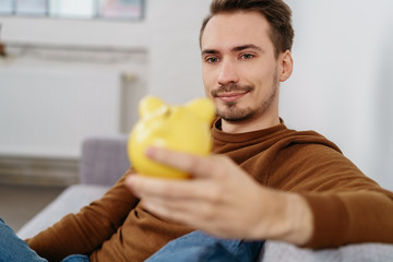 Man holding yellow piggy bank
