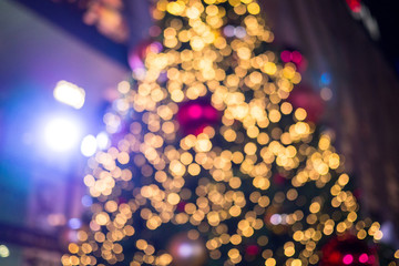 Colorful blurry Christmas tree background with lights and ornamental decorations, blurred holiday background