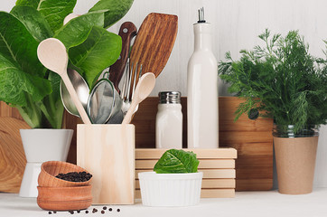 Elegant light kitchen interior with wooden utensils, ceramics and green greens in pot on white wood shelf.