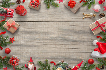 Christmas decorations background image with free space for greeting text. Christmas tree, gifts, car, lantern; pinecones; Santa hat, doll and Christmas balls. Top view of wooden table.