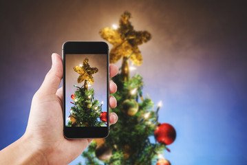 Hand holding mobile smart phone, with Christmas star on Christmas tree and decorations, colorful lights