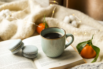 Close up blue coffee cup on the open book with cotton flower, clementine mandarin, french macaroons, plaid, and glowing christmas lights on the window sill. Cosiness, holiday morning comfort concept