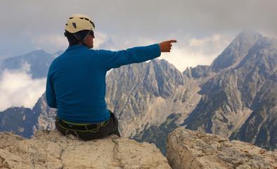 Climber showing on the mounatin peak