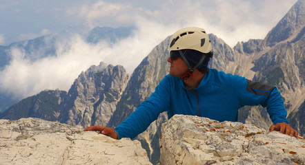 Climber leaning against a rock with a mountain landscape on bacground, Triglav National Park, Slovenia