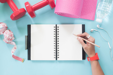 Woman hand holding pencil on blank notebook with sport and Yoga equipments on pastel color background