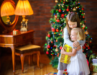 Christmas morning, two sisters give gifts and cuddles standing near a Christmas tree.