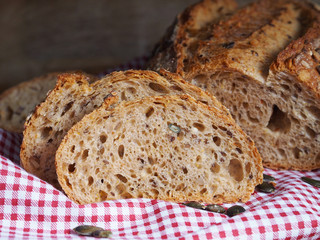 Grain bread and pumpkin seeds on dishtowel and wooden background