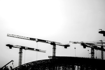 Silhouette of lattice crawler crane at construction site black and white background with copy space