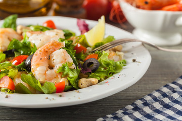 Shrimp salad with tomato, olives and cashew nuts.
