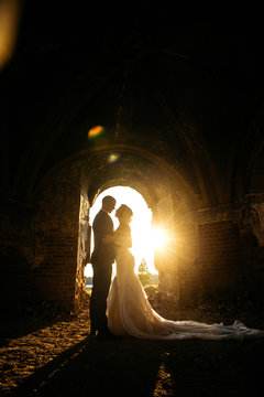 Bride and groom embracing in a dark abandoned church, sunset and sunlight on the background