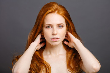 Redhead woman with strong healthy hair portrait. ginger girl shows natural hair strength