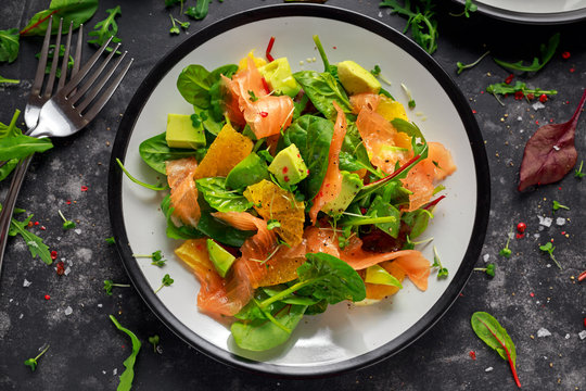 Fresh salmon salad with avocado, orange and green vegetables.