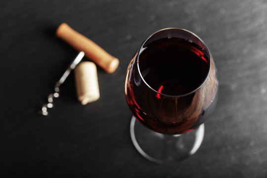 wine glass of red wine with a corkscrew. On a black wooden background. with space for text