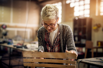 Close up view of hardworking professional carpenter woman standing with an electric drill and making or fixing a chair in the workshop.