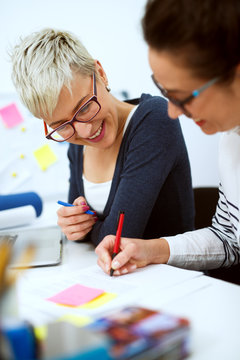 Close up of two smiling innovative stylish business middle aged women working together on problem solving while sitting in the office one next to another.