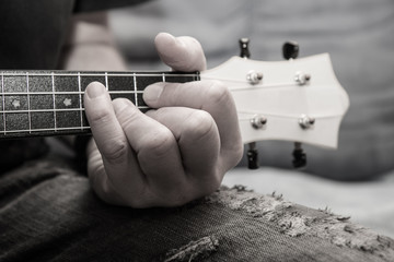 A man plays ukulele Detail of the Hand