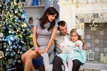 Happy family couple give gifts in the living room, behind the decorated Christmas tree, the light give a cozy atmosphere. New Year and Xmas theme