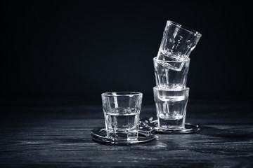Glasses with handcuffs on dark background. Alcohol dependence concept