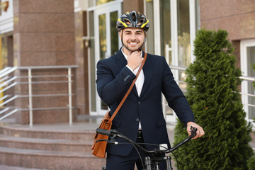 Young handsome businessman with bicycle outdoors