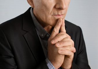 Thoughtful mature man in dark suit on light background