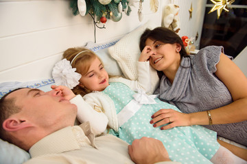 Mother, father and baby having fun in bedroom. People relaxing at home. Winter holiday Xmas and New Year concept