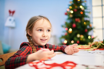 Creative little girl drawing Christmas card for her granny with wax crayons while sitting at desk of cozy living room, portrait shot