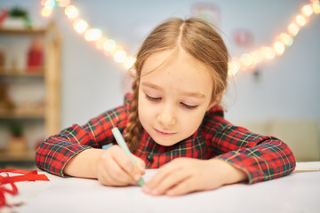 Head and shoulders portrait of little dark-haired girl wearing tartan dress wrapped up in drawing Christmas card while sitting at desk of cozy living room