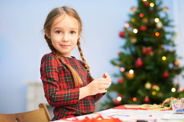 Waist-up portrait of adorable little girl looking at camera with warm smile while standing at desk and preparing Christmas surprise for her parents, decorated Christmas tree behind her