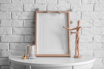 Mockup of blank frame with mannequin on table