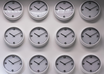 Rows of white plastic wall watches on the white background.