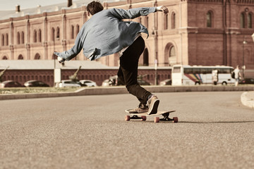 Lifestyle picture of professional rider rolling down street on skateboard at high speed with his denim shirt waving in wind, feeling free and relaxed. Unrecognizable guy skateboarding outdoors alone