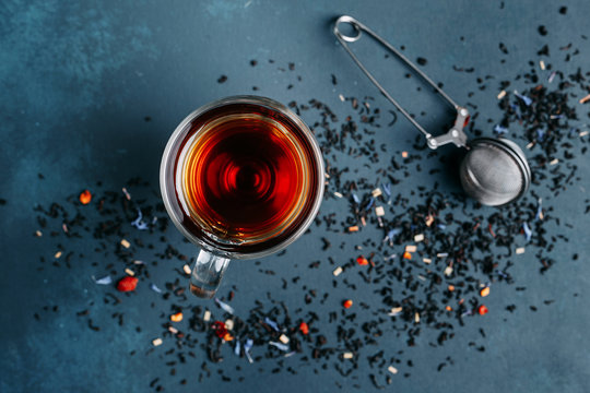 Glass cup of black tea, tea stainer and sprinkled tea leaves on dark background