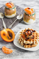 Homemade waffles are poured tamarillo on a rustic background. Yogurt with passion fruit and apple puree in small jars.