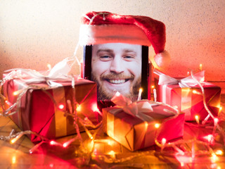 digital tablet with bearded male on screen with Christmas attributes around