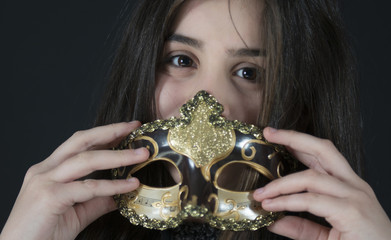 Portrait of a little girl partially covering the face with a mask
