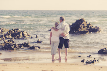 lovely senior mature couple on their 60s or 70s retired walking happy and relaxed on beach sea shore in romantic aging together