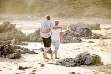 lovely senior mature couple on their 60s or 70s retired walking happy and relaxed on beach sea shore in romantic aging together and retirement