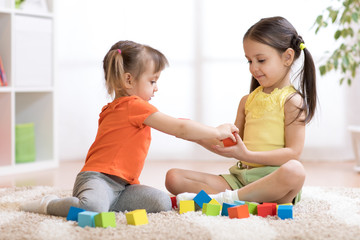 Cute children playing while sitting on carpet at home