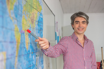 Male teacher in the classroom teaching geography pointing to a world map