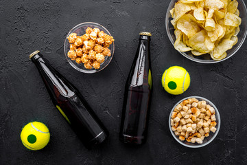 Snacks for watching sport matches and games on TV. Crisps, popcorn, rusks near drink and ball on black background top view