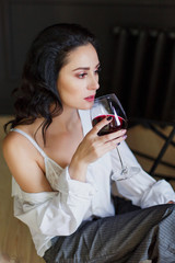 beautiful business woman in studio. He drinks wine, is casually dressed in a shirt and wide pants. portrait