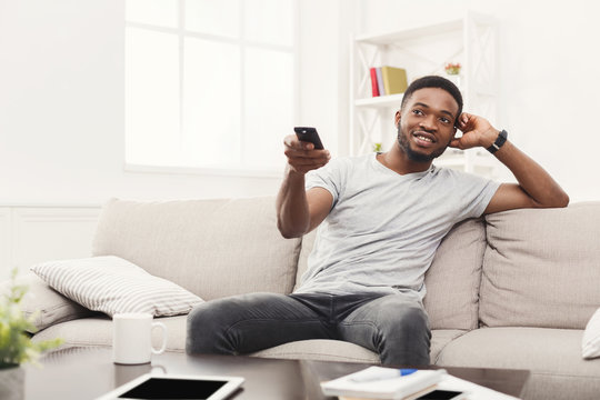 Young man watching tv using remote controller in living room